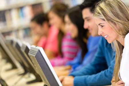 biblioteca: Grupo de estudiantes en la biblioteca el uso de computadoras Foto de archivo