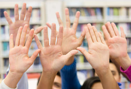 Students raising their hand wanting to participate in class photo