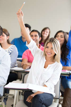 Female student participating in class and raising her hand  photo