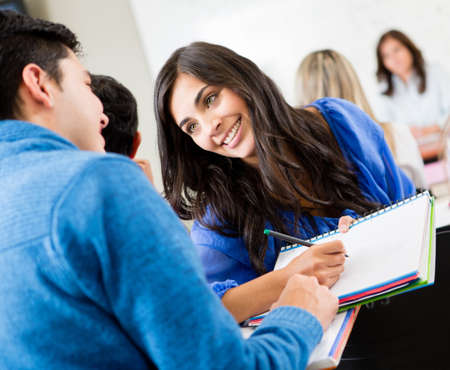 Couple of students talking in class and smiling photo