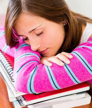 Tired female student falling asleep while studying  photo