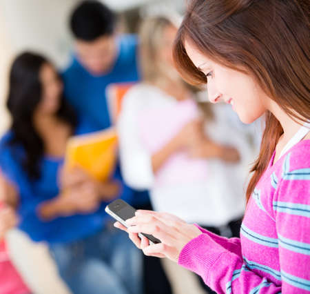 mobile apps: Female student texting on her mobile phone