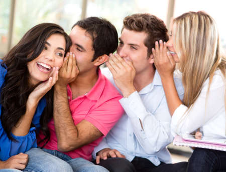 whispering: Group of students gossiping at the university
