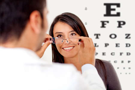 doctor of optometry: Woman wearing glasses after taking a vision test at the doctor  Stock Photo