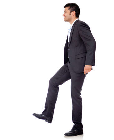 upstairs: Businessman climbing imaginary stairs - isolated over a white background  Stock Photo