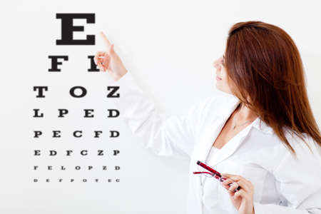 Female eye doctor making a vision test with letters on a board  photo