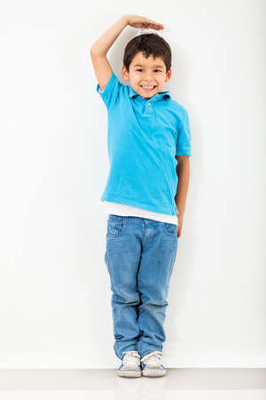 Boy growing tall and measuring himself on the wall photo