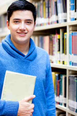 Young man at the library holding a book and smiling  photo