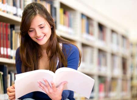 lezing: Vrouw lezend in een boek in de bibliotheek