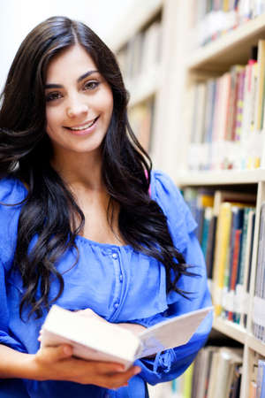 Beautiful girl at the library holding a book and smiling  photo