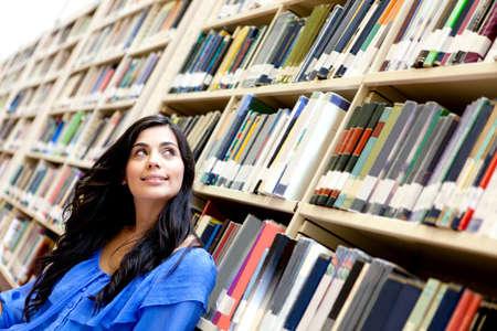 mujer pensativa: Mujer pensativa en la biblioteca rodeado de libros