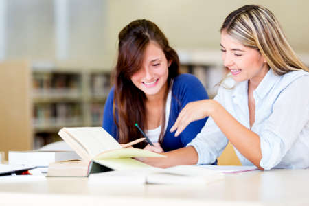 adults learning: Happy female students at the library studying  Stock Photo