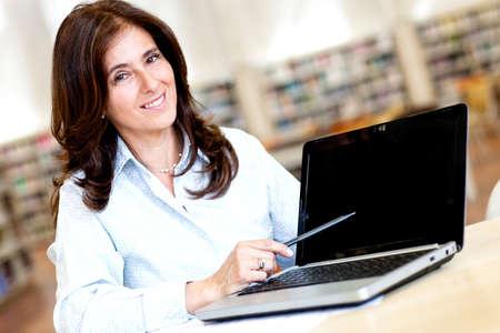 femme professeur: Enseignante avec un ordinateur portable � la biblioth�que