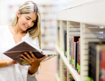 Beautiful woman reading a book at the library  Stock Photo - 14197143