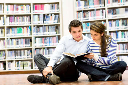 Couple of students at the library reading a book  photo