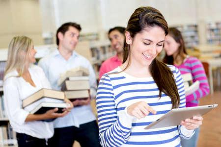 bibliotecas: Mujer con un lector de libros electr�nicos, mientras que llevar los libros amigos Foto de archivo