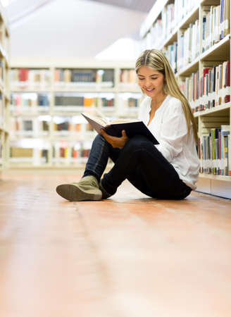 Female student at the library reading a book Stock Photo - 14231327