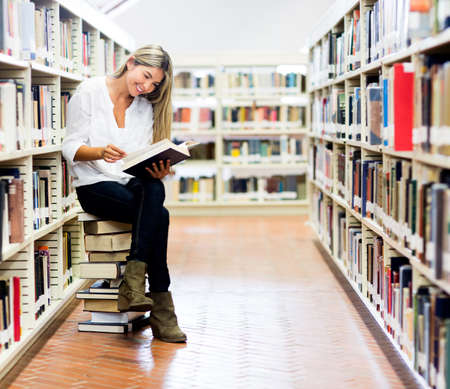 readers: Woman reading at the library sitting on a pile of books  Stock Photo