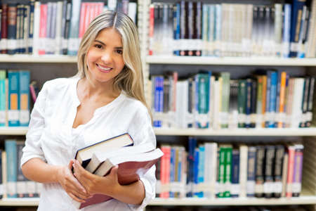 academics: Happy female student carrying books at the library  Stock Photo