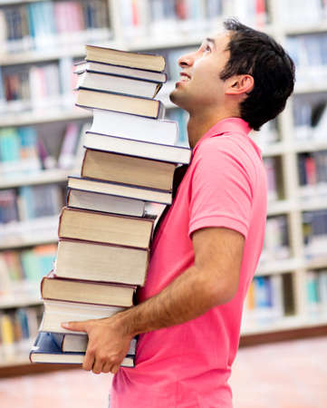 Student at the library carrying heavy books  photo