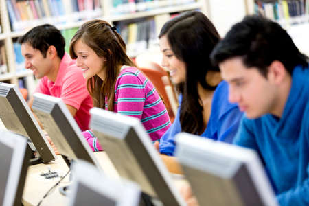 com: Group of young people studying at the library using computers