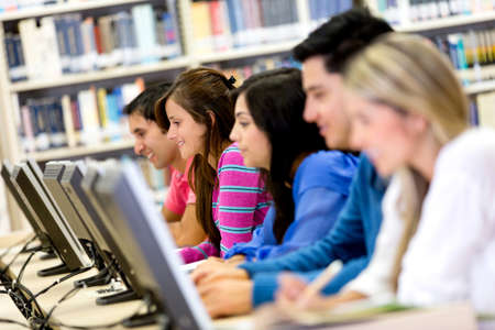 com: Group of students using computers at the library  Stock Photo
