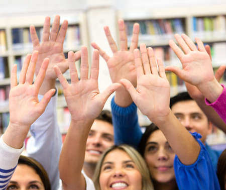 raising hand: Group of students raising their hands to participate in class