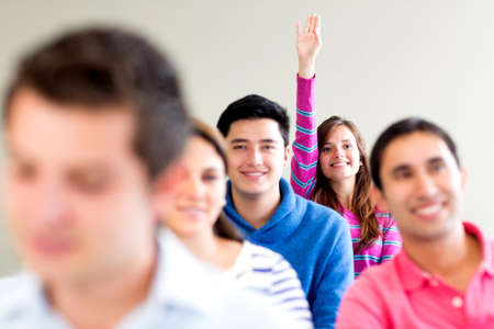 raising hands: Woman in class raising her hand to participate