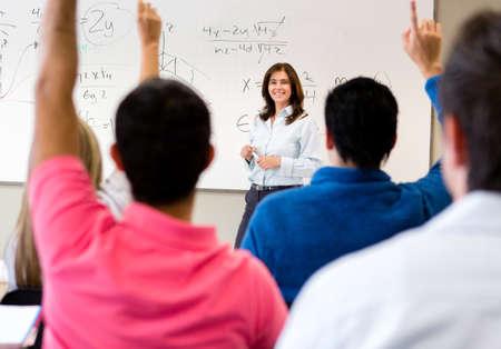 salon de clases: Los estudiantes en clase haciendo preguntas a la maestra