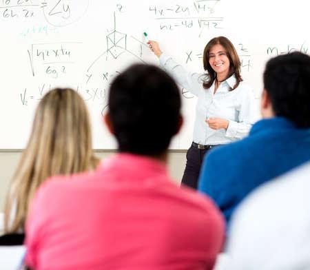 profesor: Maestro dando una conferencia en un aula y escribir f�rmulas matem�ticas en el pizarr�n
