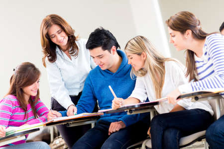 college professor: Teacher helping a group of students at the university  Stock Photo
