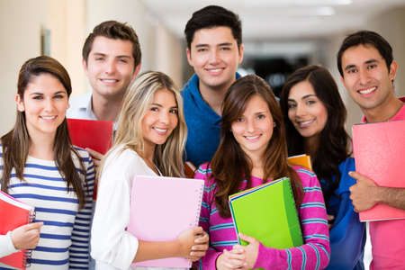 male student: Happy group of college students smiling and holding notebooks