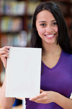 Happy young woman holding a book at the library  photo