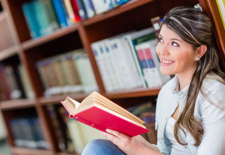 Pensive young woman reading a book at the library  photo