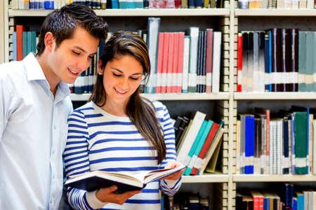 bibliotecas: Pareja de estudiantes en la biblioteca leyendo un libro