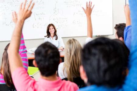 preguntando: Los estudiantes que levantan sus manos y hacer preguntas al profesor