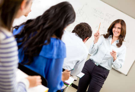 teacher teaching: Friendly woman teaching a class and smiling  Stock Photo