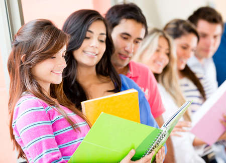 latin students: Group of college students looking at notebooks  Stock Photo