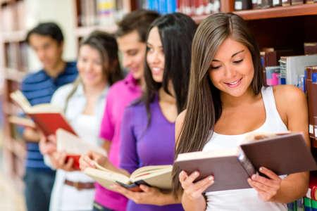 personas leyendo: Grupo de jóvenes que leen libros en la biblioteca