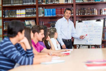 profesor: Profesor de sexo masculino con un grupo de estudiantes universitarios en la clase Foto de archivo
