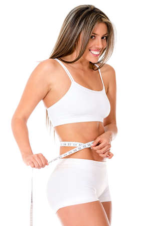 Fit woman measuring her body - isolated over a white background  photo