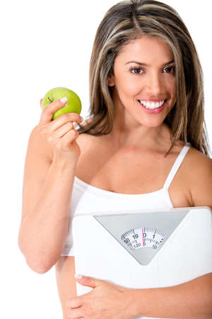 Woman dieting eating healthy and holding a scale - isolated over white  Stock Photo - 14318117