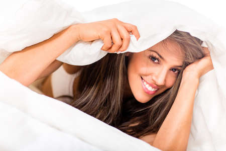coquettish: Beautiful woman in bed under the sheets