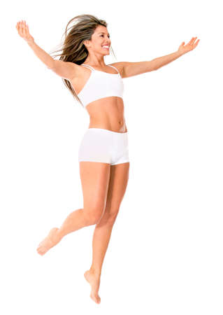 Confident woman jumping in her underwear - isolated over a white background  photo
