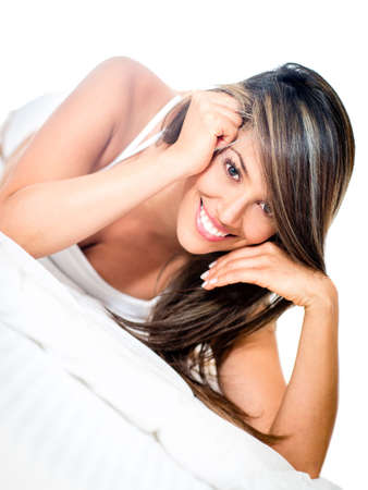 Beautiful woman lying in bed and smiling - isolated over white  photo