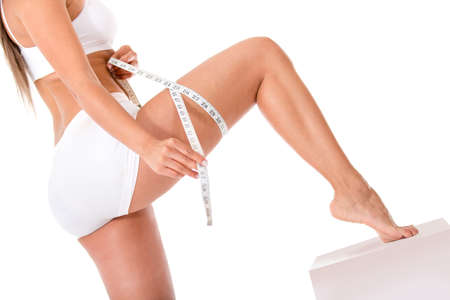 Woman measuring her leg - isolated over a white background  photo