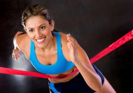 mujer deportista: Ganador de la atleta cruza la l�nea de meta Foto de archivo