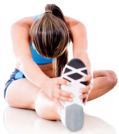 gimnasio: Una mujer estirando la pierna Atl�tico - aislados en un fondo blanco Foto de archivo