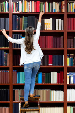 Woman at the library trying to reach a book  photo