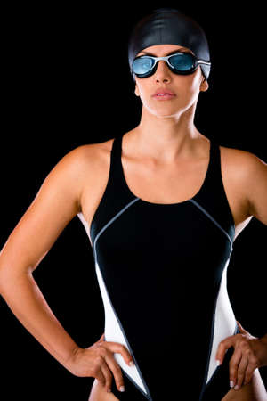 Professional female swimmer with goggles and a hat - isolated over a black background Stock Photo - 14422290